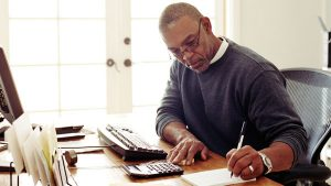 Black male writing in professional office.